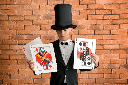 Cute little magician with cards against brick wall