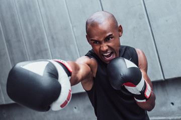 Dangerous and aggressive. Picture of young man in boxing gloves exercising against grey background outdoors