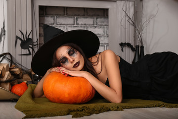 Beautiful woman dressed as witch in room decorated for Halloween