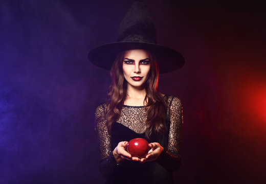 Beautiful woman dressed as witch for Halloween with apple on dark color background