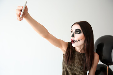 Beautiful woman with Halloween makeup and balloons taking selfie on light background