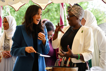 Meghan, Duchess of Sussex helps to prepare food at the launch of a cookbook with recipes from a group of women affected by the Grenfell Tower fire at Kensington Palace in London