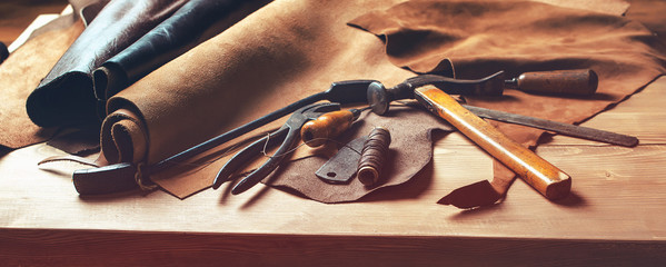 Shoemaker's work desk. Tools and leather at cobbler workplace. Set of leather craft tools on wooden background. Shoes maker tools on wooden table.