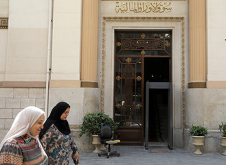 People walk in front of the Egyptian Stock Exchange in Cairo