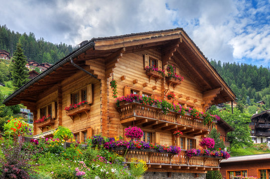 Beautiful traditional wooden house in the alpine village Grimentz, Switzerland, in the canton Valais, municipality Anniviers, with geranium flowers on the balconies