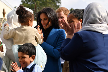 Meghan, Duchess of Sussex and Britain's Prince Harry, gather for a family picture during  the launch of a cookbook with recipes from a group of women affected by the Grenfell Tower fire at Kensington Palace in London