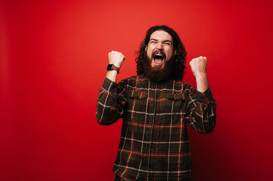 Portrait of a satisfied casual bearded hipster man celebrating success isolated over red background