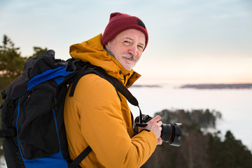 Portrait of mature man with grey beard exploring Finland in winter. Traveler Taking pictures on the top of rock. Beautiful view of northern landscape with frozen Baltic Sea and snowy islands.