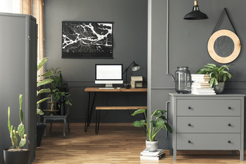 Black poster on grey wall above desk with mockup in home office interior with mirror. Real photo