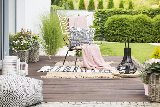 Real photo of a white pillow and pink blanket on a rattan chair standing in the garden of a luxurious house