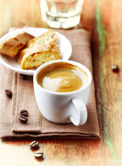 Cup of Coffee with a Biscotti. Symbolic image. Rustic wooden background.