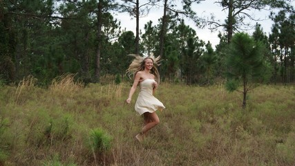 Beautiful blonde young woman similing, dancing, jumping, running and having fun on a field