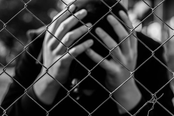 Young unidentifiable teenage boy  holding hes head at the correctional institute in black and white, conceptual image of juvenile delinquency, focus on the wired fence.