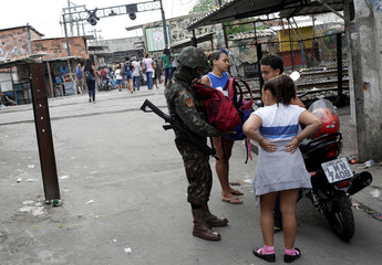 A Brazilian soldier searches the backpack of a schoolgirl during an operation against drug gangs in Jacarezinho slum in Rio de Janeiro