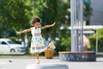 A happy black child. Little African American girl dances in the city square.