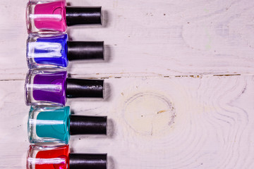 Different nail polishes on a wooden table. Top view