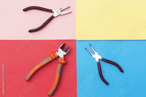 three types of pliers and nail isolated on colorful