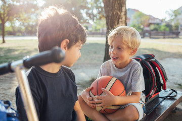 Two boys sitting on bench with basketball ball