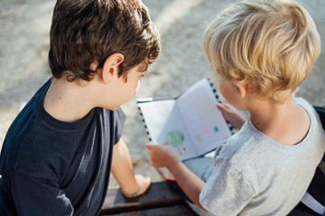 Two boys reading notebook sitting on bench at school.