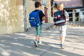 Two happy boys going to school.