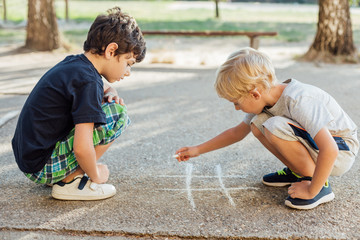 Two boys drawing on asphalt using chalk