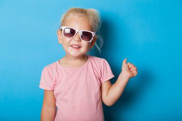 Blonde girl child in sunglasses. Attractive fashion kid.