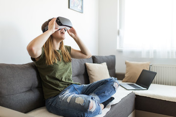 Beautiful young woman enjoying virtual reality at her home.