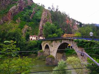 Stoned bridge crossing Nalon river between mountains, in Asturias, Spain