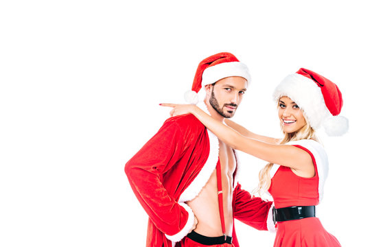smiling young woman in christmas hat and dress embracing boyfriend isolated on white background