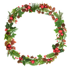 Traditional  winter and Christmas wreath garland with natural flora and fauna and red bauble decorations on white background. Christmas card for the festive season.