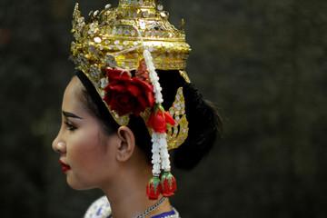 A Thai traditional dancer wears a crown while she takes a break at Erawan Shrine in Bangkok