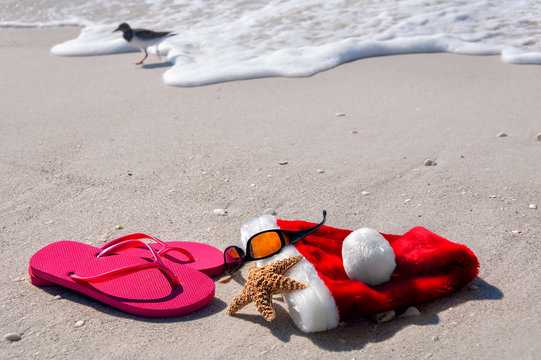 Tropical Christmas at the beach, with flip flops, sunglasses, a starfish and santa hat.