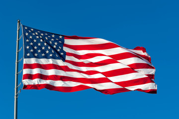 An American flag flying in the breeze against a cloudless bright blue sky.