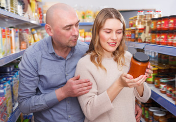 Adult family couple discussing in the food store