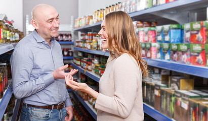 Family couple in the shop standing near shelves in grocery section
