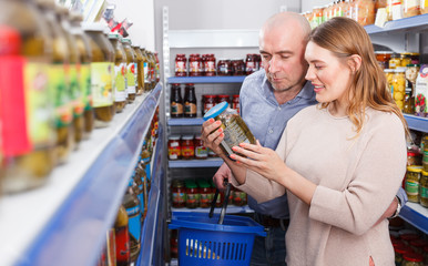couple with basket buying canned goods