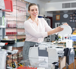 Female customer  trying kitchen rack in the tableware store