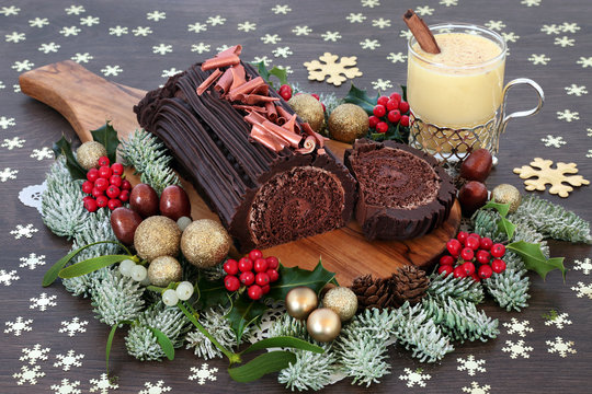 Chocolate yule cake with eggnog, traditional winter flora, gold baubles and snowflake decorations on rustic oak wood background. Festive sweet food for Christmas.