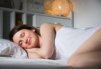 Young woman in pygama is sleeping  on bed in bedroom