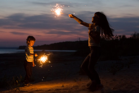 happy smiling children with Sparklers on the beach at night.