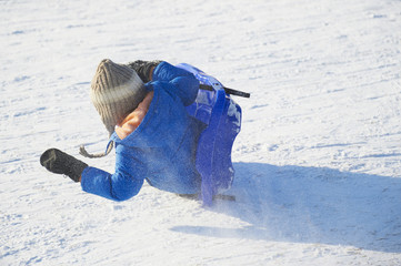 Child boy riding a bobsled. Having fun on the snow. Children winter activities.