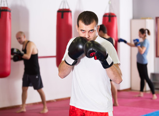 serious sportsman in the boxing hall practicing boxing punches