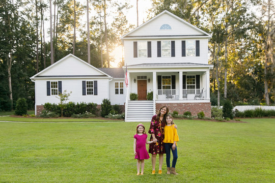 Mom and Two Daughters Hugging Outside their New Farmhouse Home