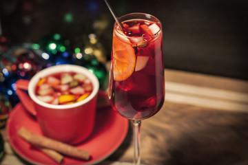 Бокал и чашка с глинтвейном на деревянном фоне с новогодними огнями