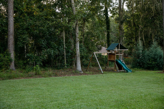 Suburban Backyard with Swingset and Grassy Lawn