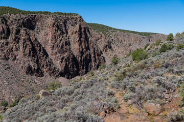 Narrow hiking trail leading through a rugged landscape and sage brush towards a rocky cliff in the Rio Grande del Norte National Monument in northern New Mexico