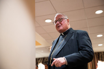 Archbishop of New York Cardinal Timothy Dolan leaves after finished a news conference in Manhattan