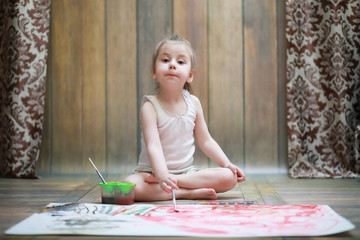 Little children paint on a large sheet of paper