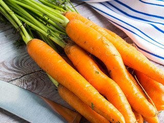 Raw carrots on rustic wooden background. Cooking vegetables