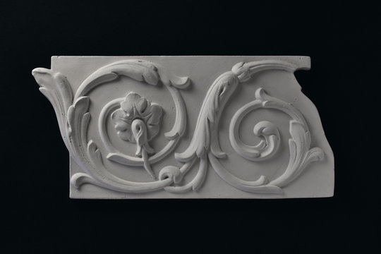 White stucco frieze and acanthus leafs witha flower.